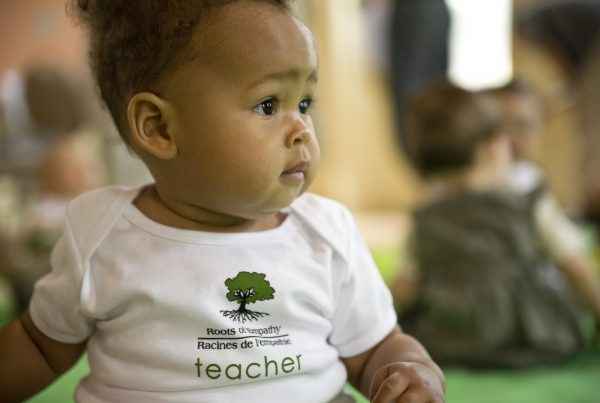 a baby in a Roots of Empathy t shirt